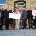 Dignitaries pose with a big cheque